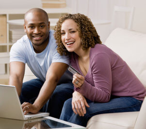 happy couple using credit card to shop online